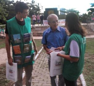 Voluntários distribuindo sacolas ecológicas